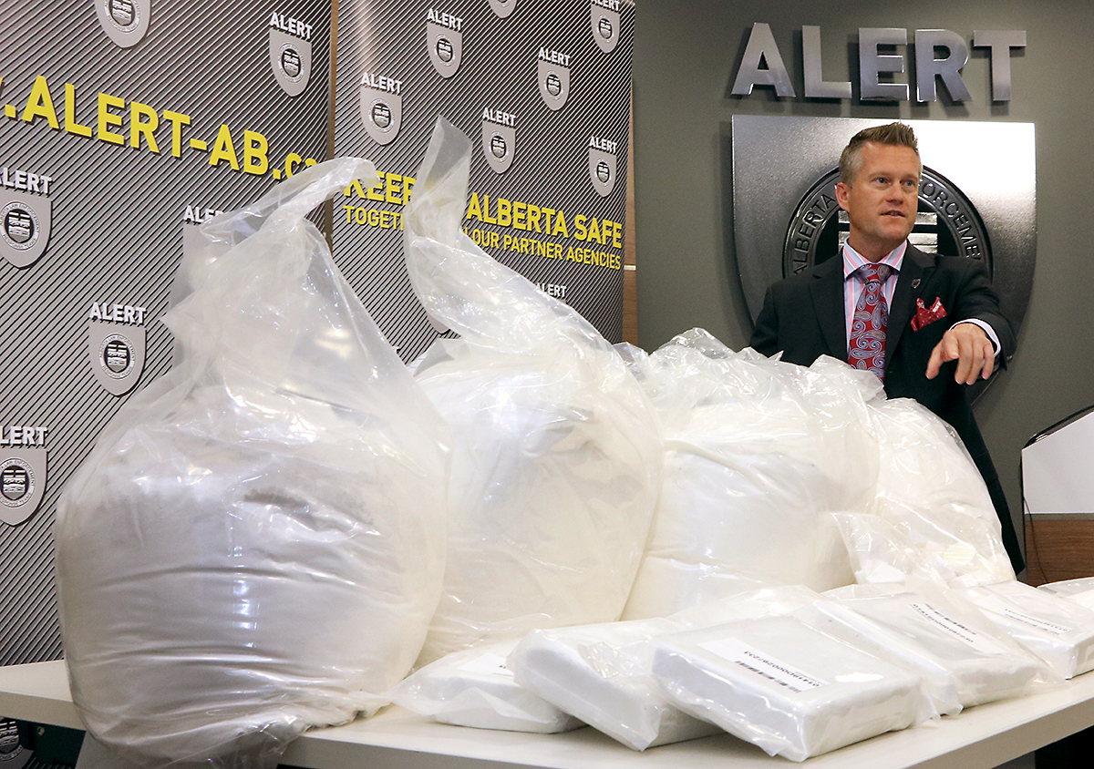 Insp. Marc Cochlin of ALERT points toward a display of drugs seized during a media availability on Thursday, July 18.